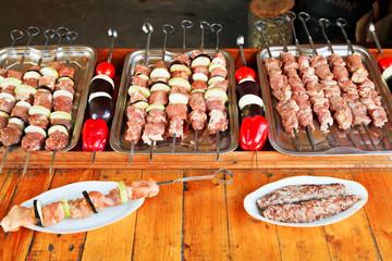 skewers of raw lamb shish kebabs and vegetables