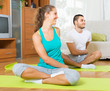 Couple practicing yoga at home