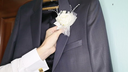 groom trying his white boutonniere trying to wedding jacket