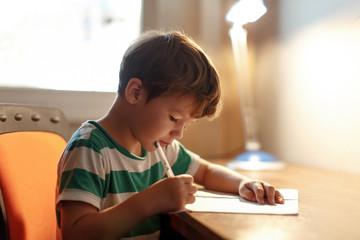 Little boy write to blank paper