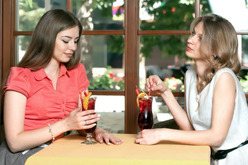 Brunette and blonde are drinking fruit drink sitting in cafe