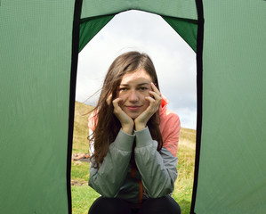 Girl with dreamy look in front of tent exit