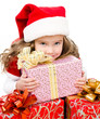 Happy cute little girl with christmas gift boxes and santa hat