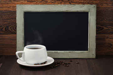 black writing board and a cup of coffee with steam