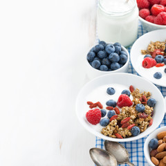 breakfast with granola, yogurt and berries on white