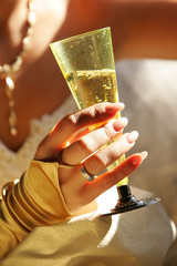 Bride is holding a glass of champagne