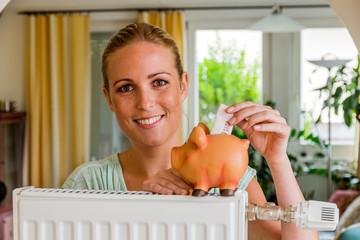 Frau mit Heizkörper und Sparschwein