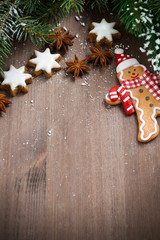 wooden background with fir branches, cookies and gingerbread