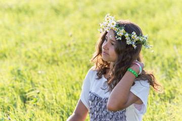 teenage girl with a wreath of daisies on the nature