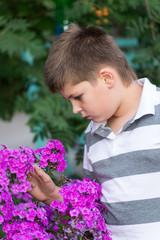 Teen boy about flowers in  garden