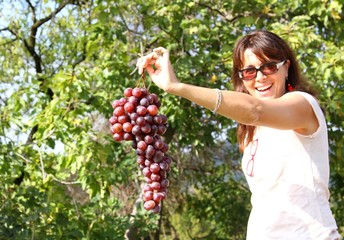 cute woman smiling with grapes on hand