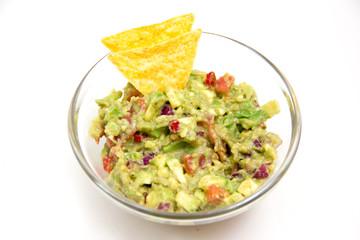 Guacamole in glass bowl on white background