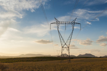 High voltage tower in the fields at sunset
