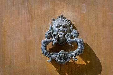 Antique knocker on a wooden door, Taormina,Sicily ,Italy.