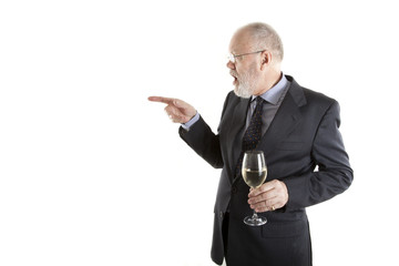 Elderly man is pointing finger with glass of white wine