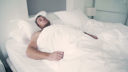Man sleeping and dreaming in bed under white quilt