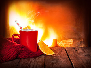 Hot warming drink in a red mug, orange slice and fireplace