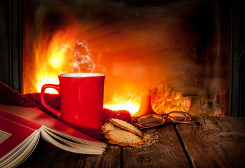 Hot tea or coffee in a red mug, book and fireplace
