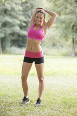 Fit sporty young woman warming up in a park