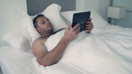 Man lying in bed under white quilt and using tablet