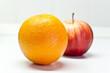 Arancia e mela su tavolo bianco