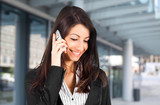 Smiling young businesswoman talking at the phone