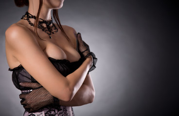 Busty woman in elegant Victorian corset embracing herself