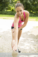 Happy young woman doing stretching exercises