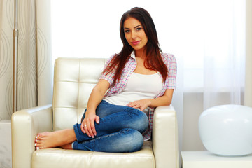 Portrait of attractive woman sitting on the sofa at home