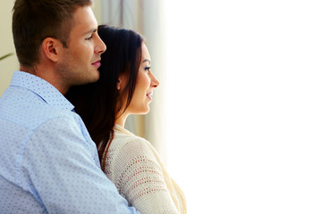 Side view portrait of a couple looking at window