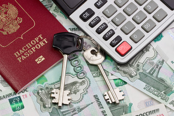 Passport, keys and the calculator on a background of money