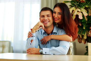 Portrait of a young happy couple hugging at home