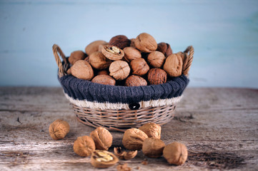 Whole walnuts piled in a basket, lighted with sun, rural scene