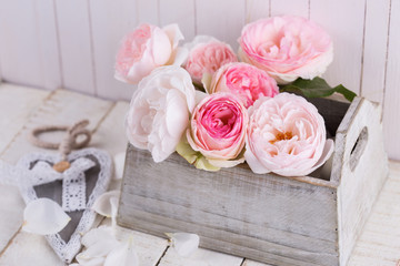 Fresh roses in box on white wooden background.