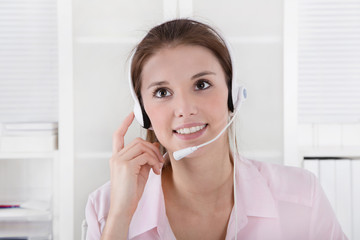 Arbeit im Call-Center: junge Frau mit Freisprecher Telefon
