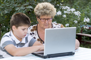 Granny with a grandson behind the laptop outdoors