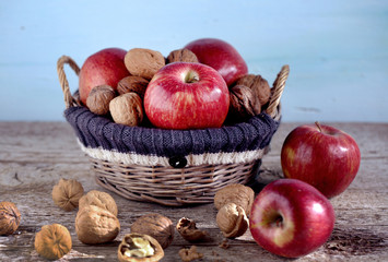 Basket full of red apples and walnuts in shells, autumn scene