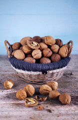 Walnut basket full of whole nuts in shells and some broken