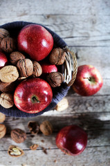 Red apples and walnuts in shells filled in basket, autumn scene