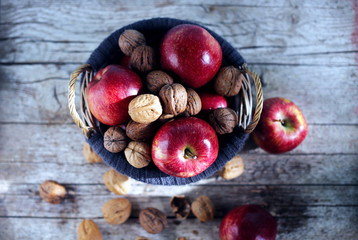 Apples and walnuts in basket, top shot, autumn sunlight