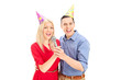 Young couple with party hats singing on microphone