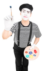 Male mime artist holding a paintbrush