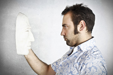Man looking to a plaster mask