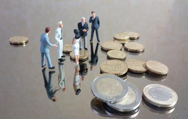 Petit groupe discutant au milieu des pièces de monnaies