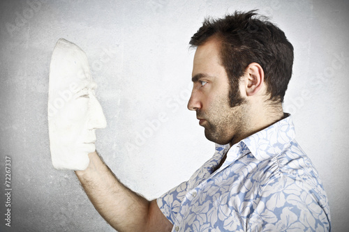 Man looking to a plaster mask Poster
