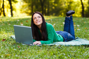 Woman using laptop in park and thinking