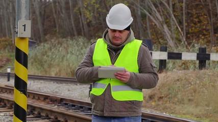 Railway engineer working with tablet PC near railway