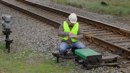 Railway engineer with tablet PC performing maintenance