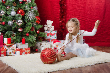 Five-year girl with balloons near Christmas tree