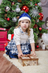 Three year old girl with a gift in Christmas tree